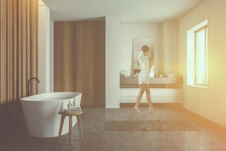 Young woman walking in modern bathroom with white and wooden walls, comfortable bathtub and round sink on stone countertop. Toned image double exposure Stock fotó - 133470617