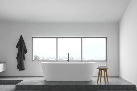 Interior of minimalistic bathroom with white walls, concrete floor, comfortable white bathtub under window and chair with towels. 3d rendering