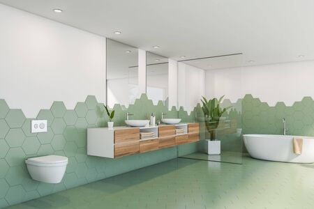 Corner of stylish bathroom with green hexagonal tile and white walls, comfortable white bathtub, toilet and double sink with mirrors on wooden countertops. 3d rendering