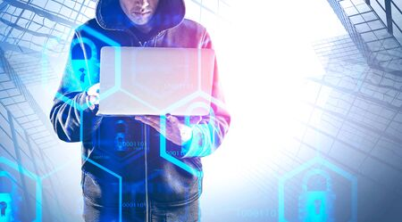Young hacker in hoodie using laptop in abstract city with double exposure of cyber security interface. Concept of phishing. Toned image copy space 写真素材