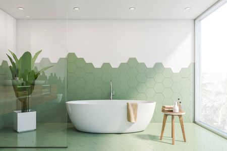 Interior of stylish bathroom with green hexagonal tile and white walls, panoramic window and comfortable white bathtub with towel on it. 3d rendering