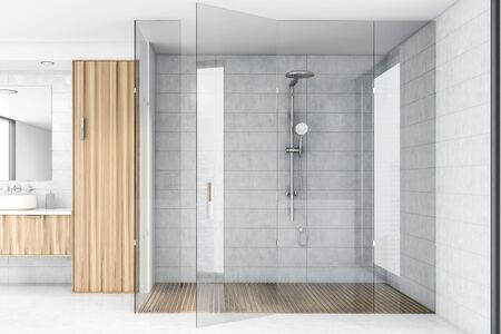 Interior of spacious bathroom with white tile walls, concrete floor, comfortable shower stall and sink on wooden countertop. 3d rendering