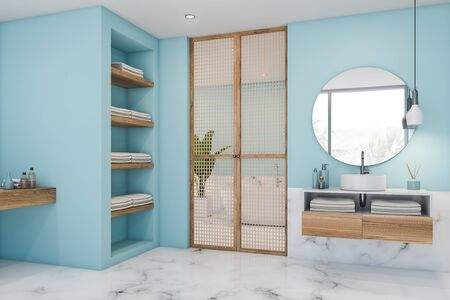 Corner of luxury bathroom with blue and white marble walls, compact sink with round mirror on wooden countertop and bathtub in background. 3d rendering Stock Photo