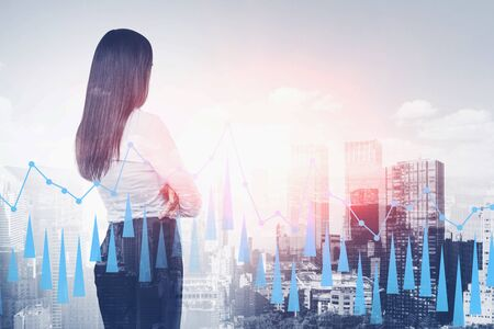Rear view of businesswoman with black hair looking at city with double exposure of graph. Concept of trading and leadership. Toned image Banco de Imagens