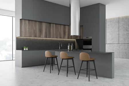 Corner of luxury kitchen with concrete walls and floor, panoramic windows, wooden cupboards and bar with stools. Built in appliances. 3d rendering