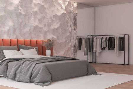 Corner of modern bedroom with crude white walls, wooden floor and comfortable orange king size bed with clothes hanging near it. 3d rendering Reklamní fotografie