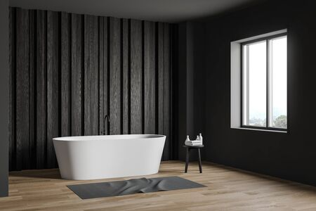 Corner of spacious minimalistic bathroom with gray and dark wooden walls, wooden floor, comfortable white bathtub and chair with towels. 3d rendering