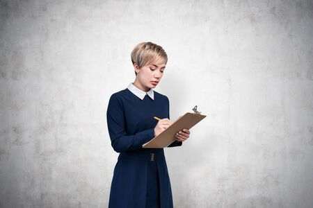 Portrait of serious young blonde businesswoman wearing blue dress writing in clipboard standing near concrete wall. Concept of planning and education. Mock up
