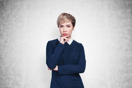Portrait of pensive young Asian businesswoman with short hair wearing blue dress standing near concrete wall. Concept of brainstorming. Mock up