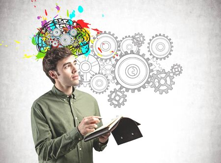 Thoughtful young man with notebook standing near concrete wall with colorful brain sketch and gears. Concept of brainstorming Stock Photo