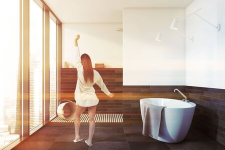 Rear view of woman in nightgown standing in stylish panoramic bathroom with white and gray walls, comfortable bathtub and shower stall. Toned image Stock fotó