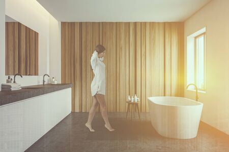 Young woman walking in modern bathroom with white and wooden walls, comfortable bathtub and double sink on stone countertop. Toned image double exposure