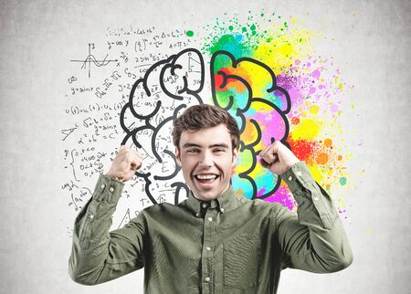 Happy young man in green shirt screaming with joy standing near concrete wall with brain sketch drawn on it. Concept of creative and analytical thinking