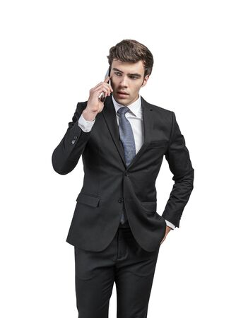 Isolated portrait of serious handsome young caucasian businessman with dark hair talking on smartphone. Concept of communication and business lifestyle. Banque d'images