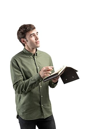 Isolated portrait of handsome young writer or designer standing with notebook and pencil and thinking. Concept of planning and imagination Reklamní fotografie