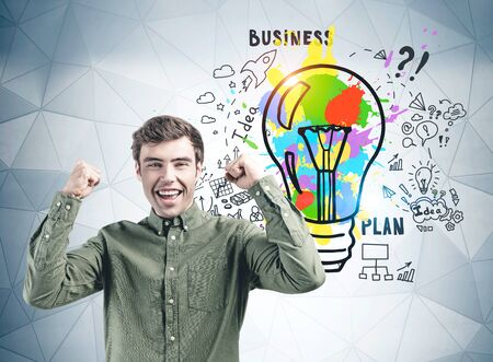 Happy young man in green shirt screaming with joy standing near gray wall with colorful business idea sketch drawn on it.