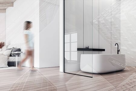 Blurry young woman walking in modern attic bathroom with white panel walls, wooden floor, comfortable bathtub and bedroom in background. Toned image double exposure Stockfoto