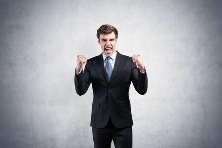 Portrait of happy successful young businessman in suit shouting with clenched fists near concrete wall. Concept of business victory and celebration. Mock up Banco de Imagens