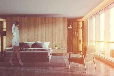Young woman walking in modern bedroom with wooden walls, concrete floor, comfortable king size bed, armchair and bookcases. Toned image double exposure