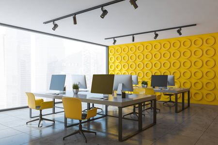 Corner of open space office with yellow geometric pattern walls, stone floor and long white computer tables with yellow chairs. 3d rendering Stock Photo - 133854578