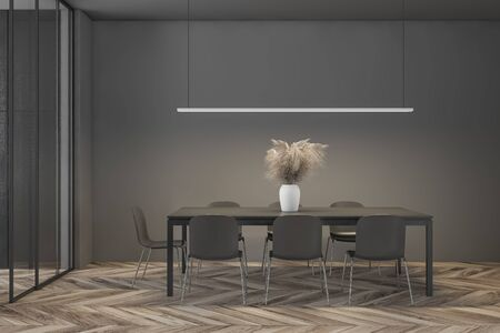 Interior of minimalistic dining room with dark grey and wooden walls, wooden floor and long black table with gray chairs. 3d rendering 版權商用圖片