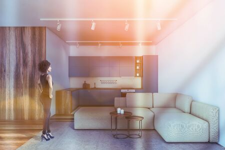 African American woman standing in modern kitchen with white and wooden walls, wooden floor, blue countertops and comfortable beige sofa with coffee tables. Toned image Stock Photo