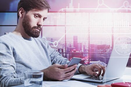 Serious young businessman in casual clothes working with laptop and smartphone in panoramic office with double exposure of digital HUD interface. Concept of big data and performance. Toned image