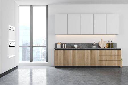 Interior of minimalistic kitchen with white walls, concrete floor, wooden countertops and white cupboards, window with cityscape and built in appliances. 3d rendering