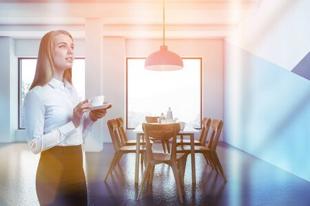 Pensive blonde businesswoman standing in modern dining room with white, blue and dark blue walls, concrete floor, and white table with wooden chairs. Toned image 版權商用圖片