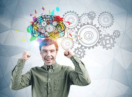 Happy young man in green shirt screaming with joy standing near gray wall with colorful brain sketch and gears. Concept of brainstorming