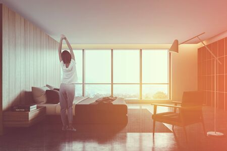 Young woman in pajamas standing in modern bedroom with wooden walls, concrete floor, comfortable king size bed, armchair and bookcase. Toned image double exposure