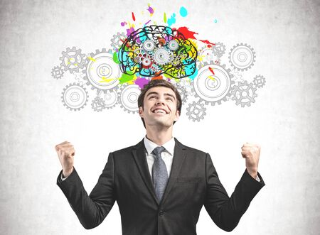 Happy young businessman standing near concrete wall with colorful brain sketch with gears drawn on it. Concept of brainstorming