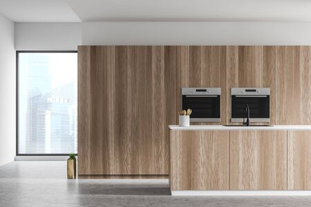 Interior of spacious loft kitchen with white walls, concrete floor, wooden countertop with built in sink and two built in ovens. 3d rendering