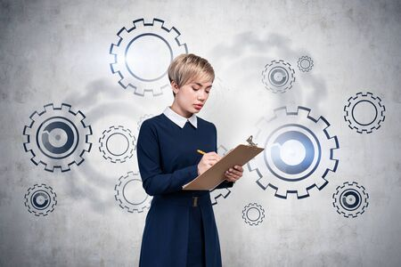 Serious young businesswoman in blue dress writing in her clipboard standing near concrete wall with gears drawn on it. Concept of teamwork.