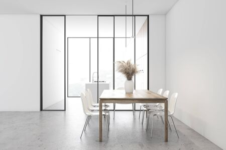 Side view of spacious dining room with white walls, concrete floor, long wooden table with chairs and panoramic kitchen with island in background. 3d rendering 版權商用圖片