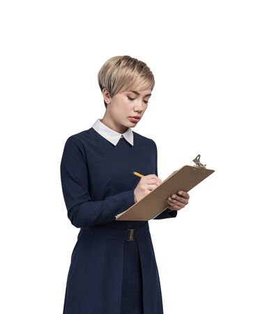 Isolated portrait of serious young blonde businesswoman wearing blue dress writing in clipboard. Concept of planning and education Фото со стока