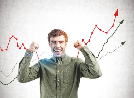 Happy young man in green shirt screaming with joy standing near concrete wall with growing graphs drawn on it. Concept of business success Banco de Imagens