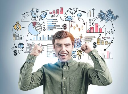 Happy young man in green shirt screaming with joy standing near gray wall with colorful business plan sketch drawn on it. Banco de Imagens