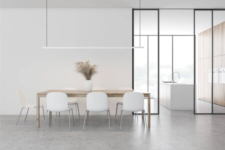 Interior of spacious dining room with white walls, concrete floor, panoramic windows and long wooden table with chairs. Kitchen in background. 3d rendering