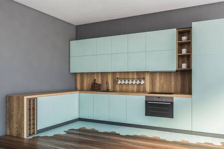 Corner of stylish kitchen with gray walls, wooden floor, blue countertops and cupboards and built in appliances. 3d rendering Stock Photo