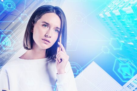 Thoughtful young woman in smart casual clothes standing in modern city with double exposure of online shopping interface. Concept of e commerce. Toned image 스톡 콘텐츠