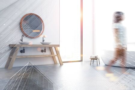 Blurry young woman walking in attic bedroom with white walls, concrete floor, comfortable bathtub and double sink with round mirror. Toned image double exposure