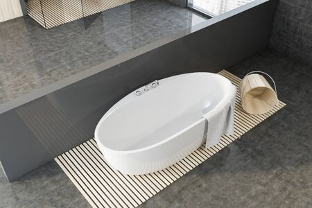 Top view of comfortable white bathtub standing in spacious bathroom interior with gray walls and concrete floor. Concept of spa. 3d rendering