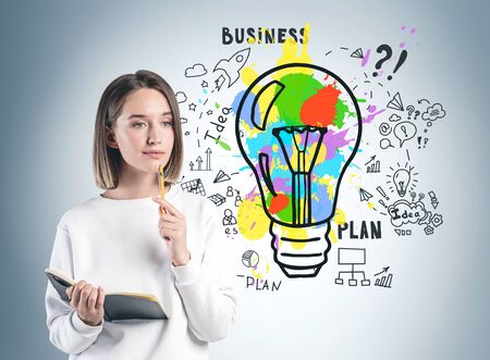 Thoughtful young woman in casual clothes with notebook standing near gray wall with colorful business idea sketch drawn on it. Concept of startup