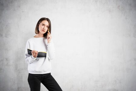 Portrait of thoughtful young woman in smart casual clothes standing with notebook and pen near concrete wall. Concept of education and scheduling. Mock up