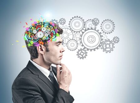 Side view of pensive young businessman standing near gray wall with colorful brain sketch and gears. Concept of brainstorming Stock Photo