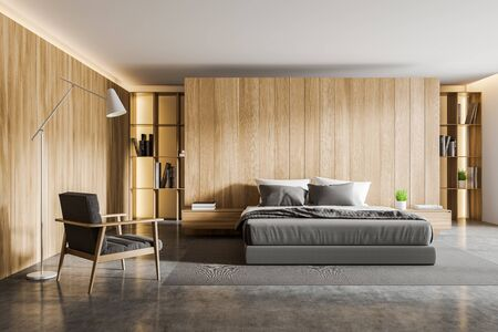 Interior of comfortable master bedroom with wooden walls, concrete floor, king size bed standing on carpet, bookshelves and gray armchair. 3d rendering