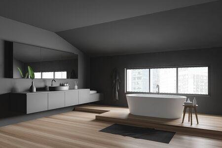 Corner of minimalistic bathroom with dark grey walls, wooden floor, comfortable white bathtub near window and round sink with big mirror. 3d rendering