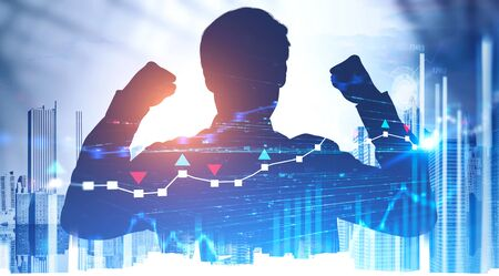 Silhouette of successful young businessman celebrating victory abstract city with double exposure of charts and HUD interface. Concept of fintech and trading. Toned image