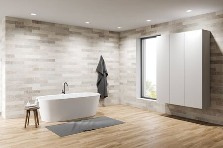 Corner of spacious minimalistic bathroom with light tile walls, wooden floor, comfortable white bathtub and wardrobe. 3d rendering